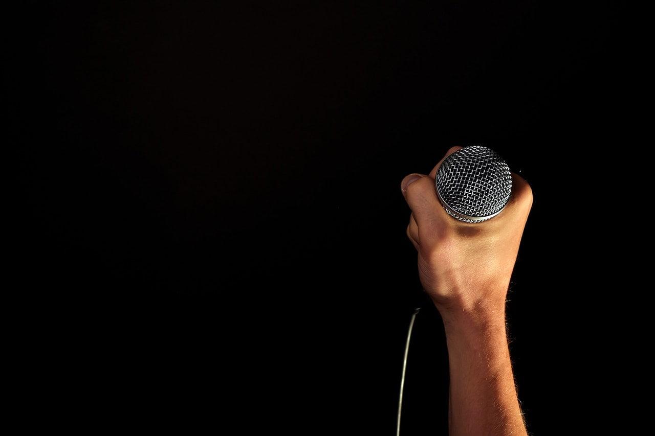 Mikrofon w ręce na czarnym tle.