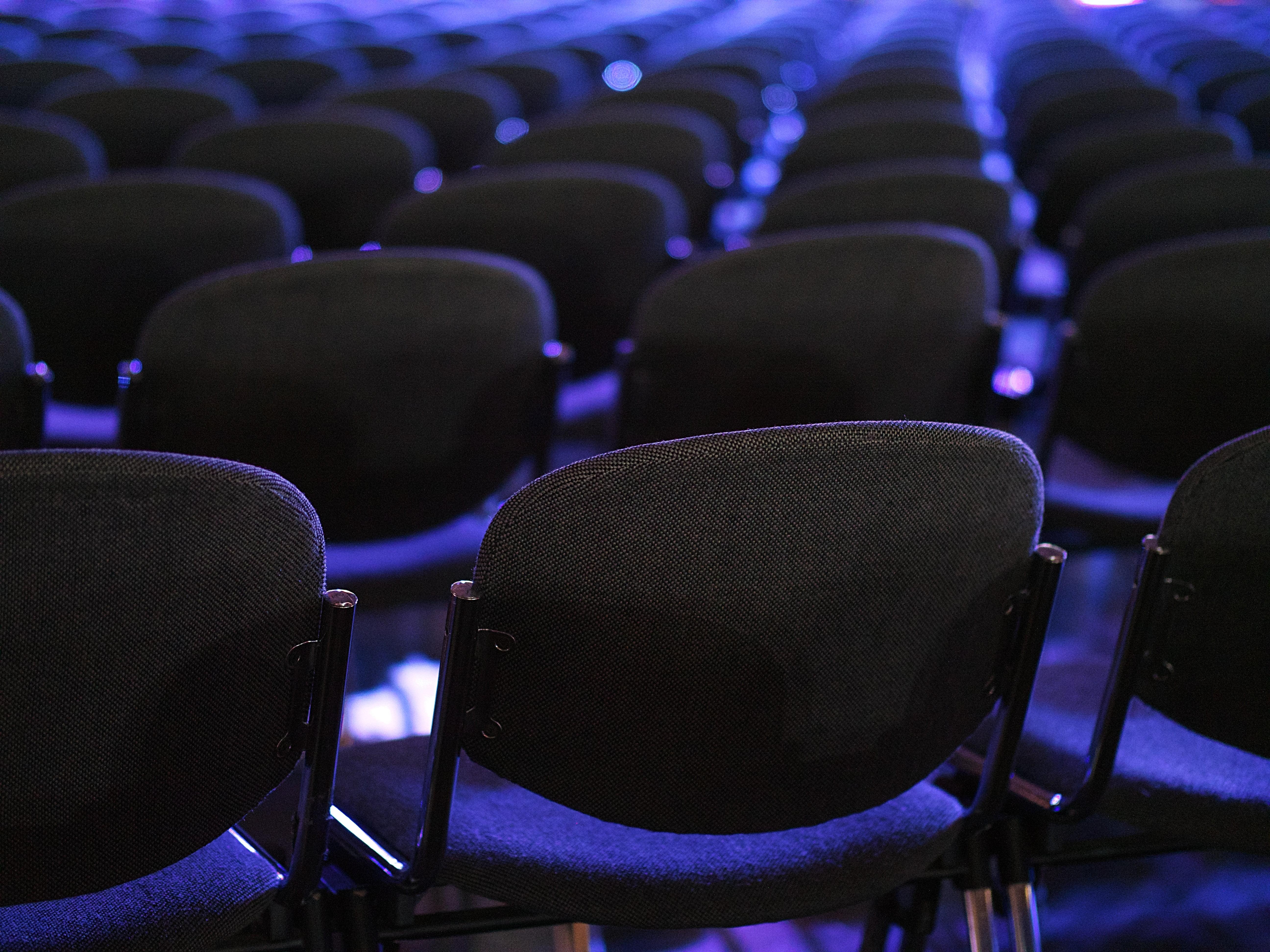 Równo ułożone krzesła podświetlone niebieskim światłem